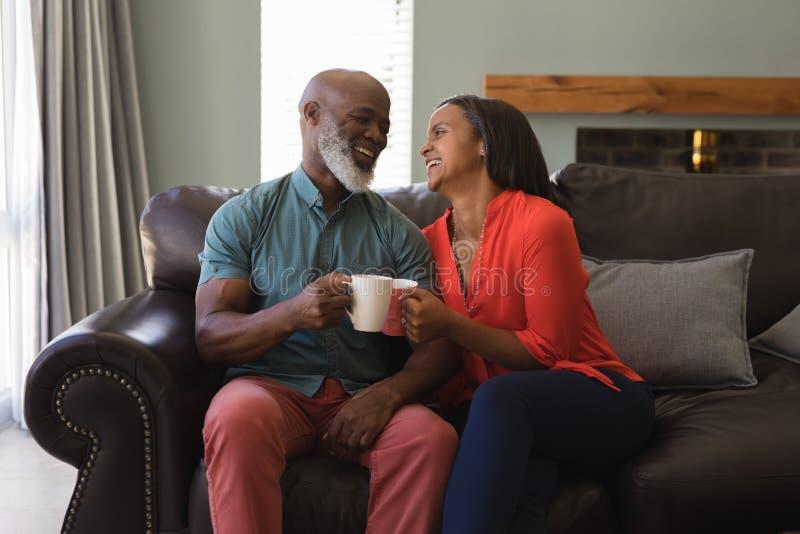 Pares superiores que comem o café na sala de visitas em casa foto de stock royalty free