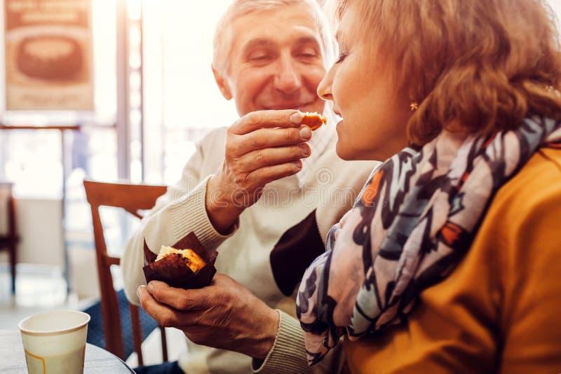Pares superiores que comem queques no café e que bebem o café Homem que alimenta sua esposa Comemorando o aniversário Valores fam fotografia de stock royalty free