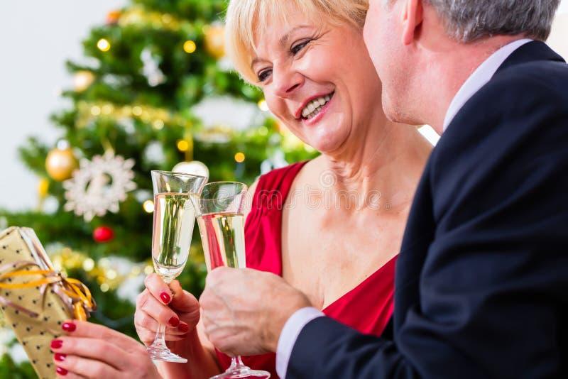 Pares superiores que comemoram o Natal com champanhe fotografia de stock royalty free