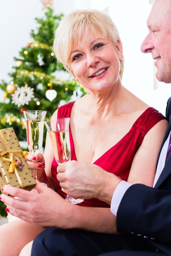 Pares superiores que comemoram o Natal com champanhe fotografia de stock