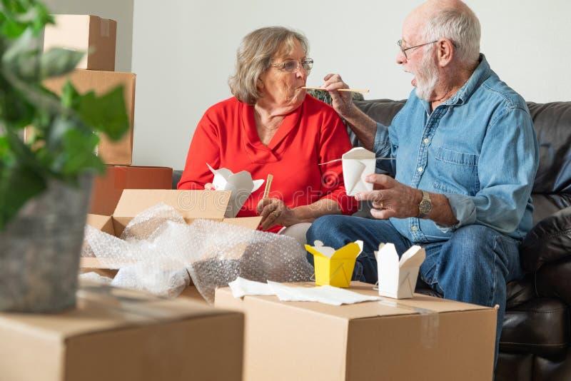 Pares superiores que compartilham do alimento chin?s cercado movendo caixas imagem de stock royalty free