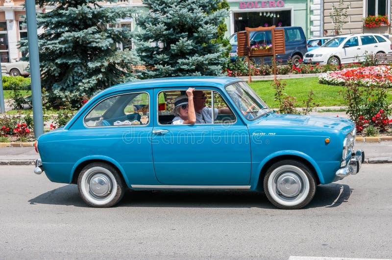 Pares superiores que conduzem Fiat azul 850 na feira automóvel local do veterano fotografia de stock royalty free