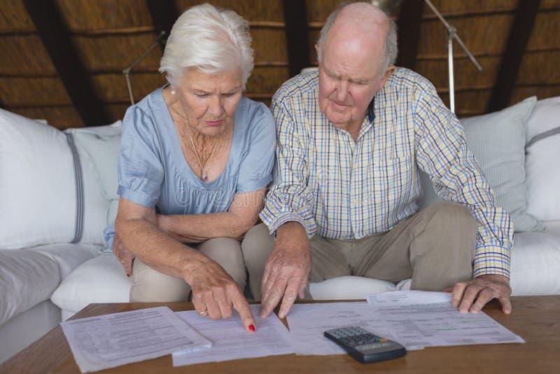 Pares superiores que discutem sobre contas médicas na sala de visitas imagens de stock royalty free