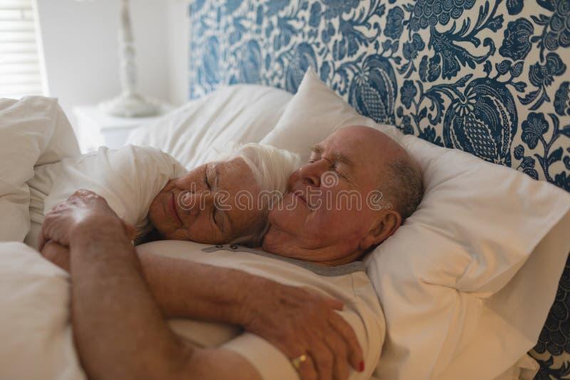 Pares superiores que dormem junto no quarto fotografia de stock