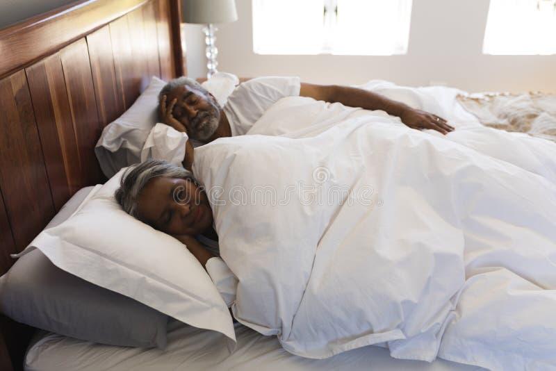 Pares superiores que dormem no quarto em casa imagens de stock