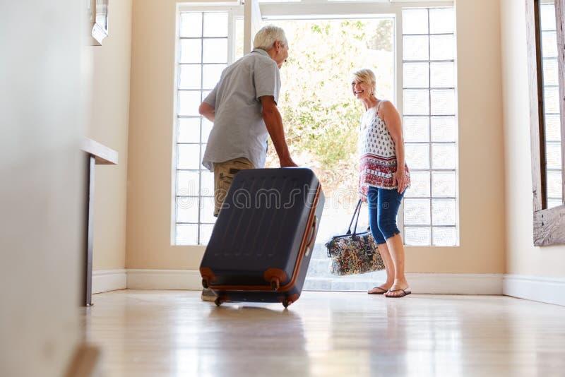 Pares superiores que estão por Front Door With Suitcase About para sair para férias fotos de stock