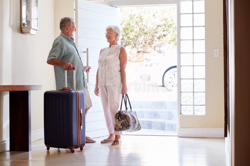 Pares superiores que estão por Front Door With Suitcase About para sair para férias imagem de stock