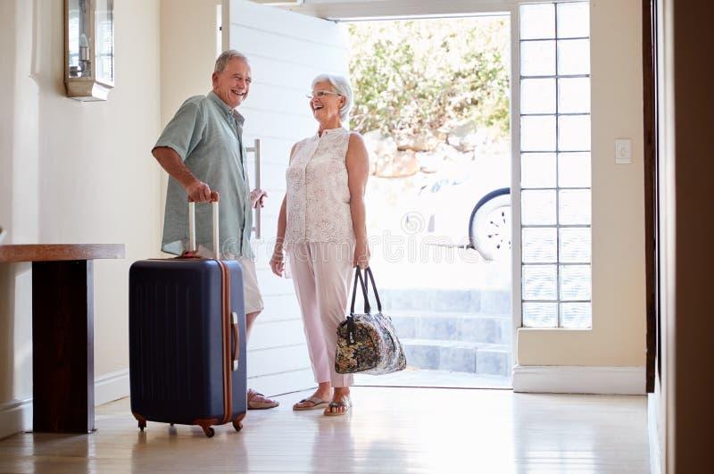 Pares superiores que estão por Front Door With Suitcase About para sair para férias fotografia de stock