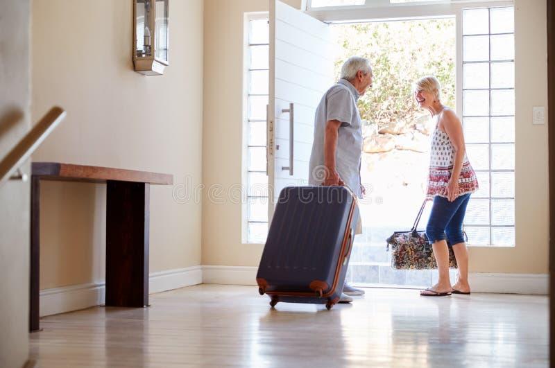 Pares superiores que estão por Front Door With Suitcase About para sair para férias imagem de stock royalty free