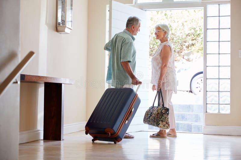 Pares superiores que estão por Front Door With Suitcase About para sair para férias imagens de stock royalty free