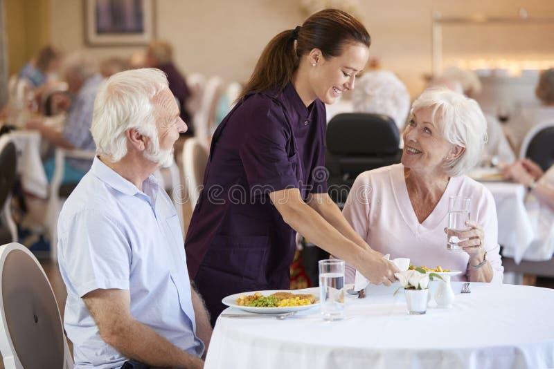 Pares superiores que estão sendo servidos com refeição pela equipe de tratamento na sala de jantar do lar de idosos imagens de stock