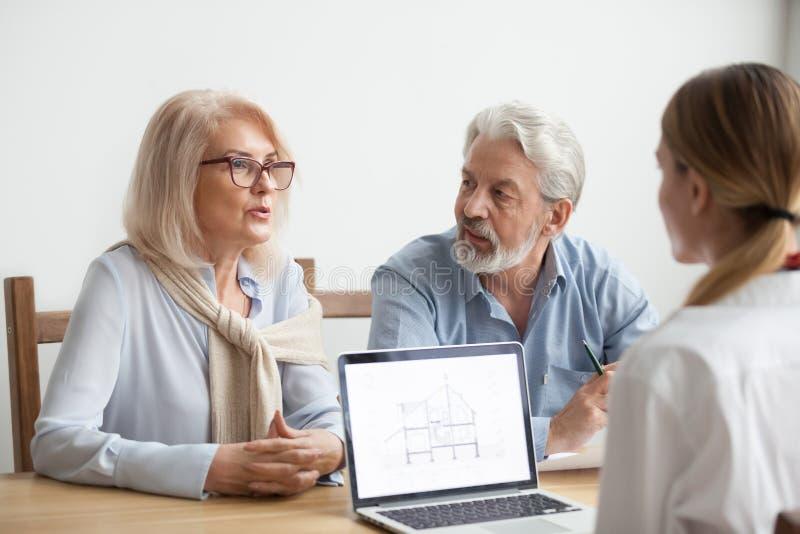 Pares superiores que falam ao agente sobre a compra da casa na reunião foto de stock
