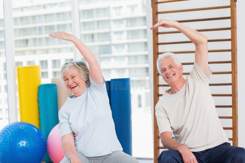 Pares superiores que fazem esticando o exercício no gym imagens de stock royalty free