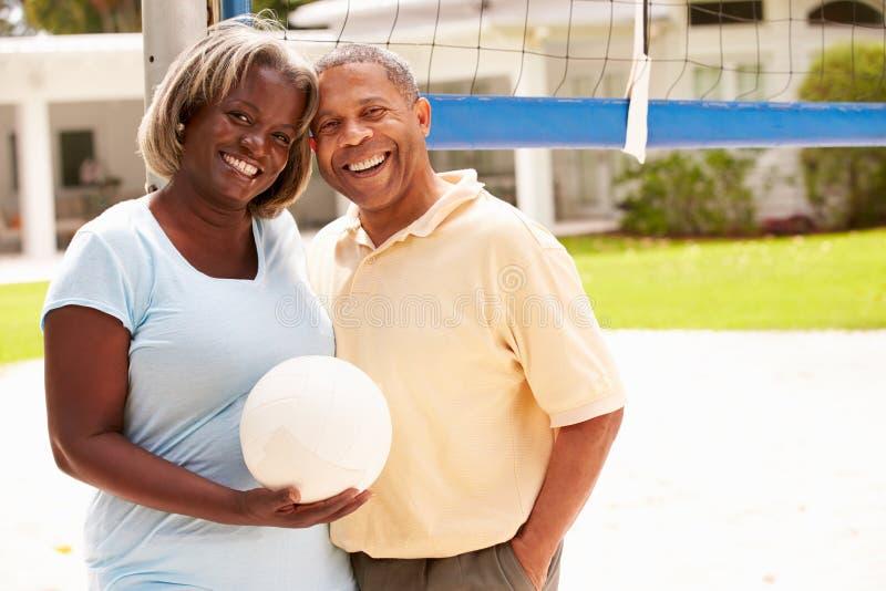 Pares superiores que jogam o voleibol junto fotografia de stock royalty free