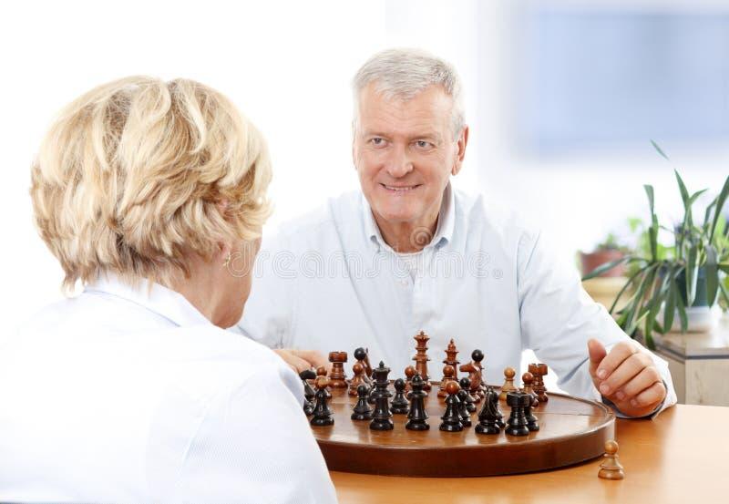 Pares superiores que jogam a xadrez foto de stock