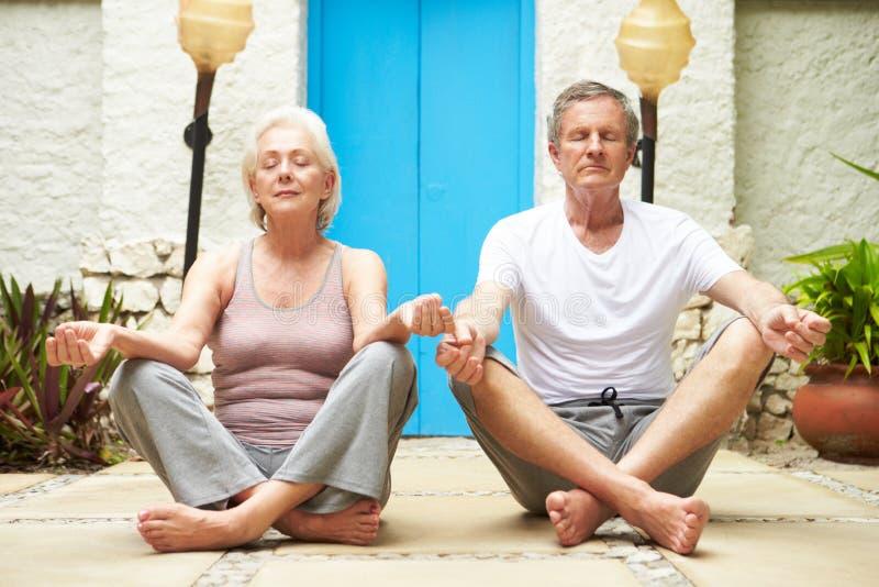 Pares superiores que meditam fora em termas da saúde imagens de stock royalty free
