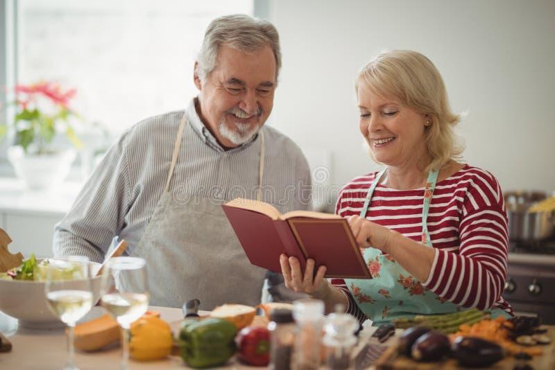 Pares superiores que preparam o alimento na cozinha imagem de stock