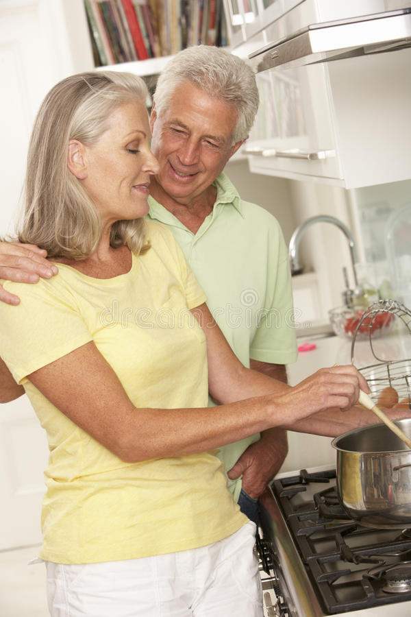 Pares superiores que preparam a refeição no fogão imagem de stock