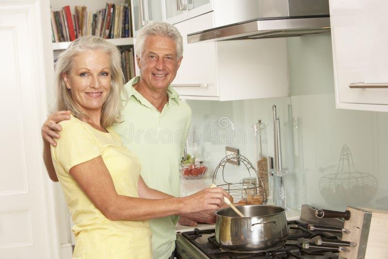 Pares superiores que preparam a refeição no fogão fotografia de stock