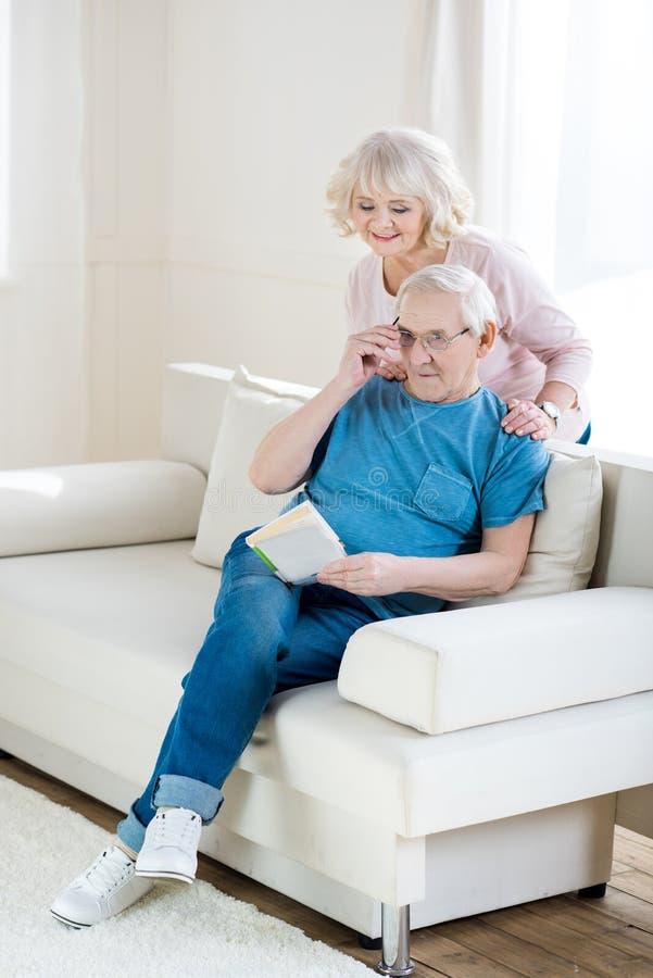 Pares superiores que relaxam em casa, livro de leitura do homem fotos de stock