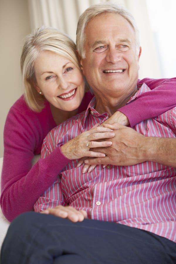 Pares superiores que relaxam em Sofa Together At Home foto de stock