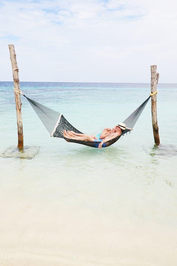 Pares superiores que relaxam na rede da praia fotos de stock royalty free