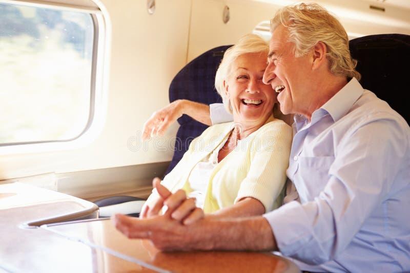 Pares superiores que relaxam na viagem de trem imagens de stock royalty free