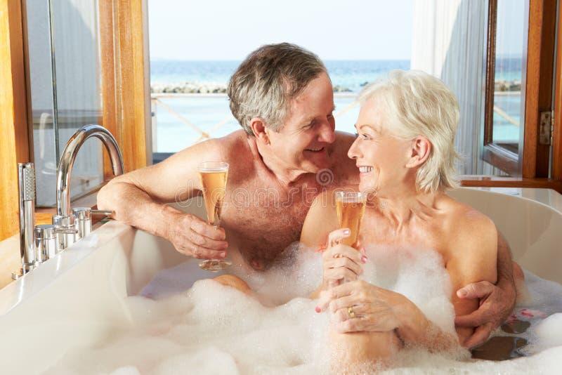 Pares superiores que relaxam no banho que bebe Champagne Together fotos de stock royalty free