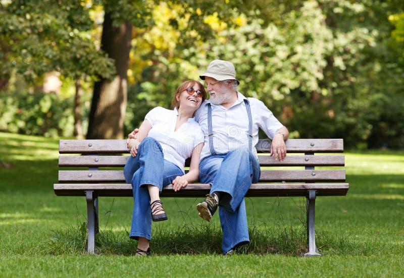 Pares superiores que sentam-se em um banco de parque imagem de stock
