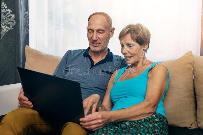 Pares superiores que sentam-se no sofá e que usam o portátil junto fotos de stock