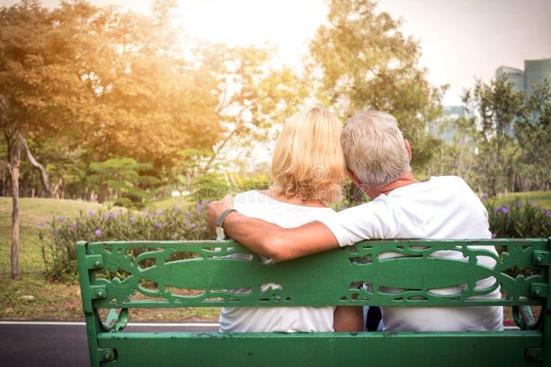 Pares superiores que situam em um banco e que têm o tempo romântico e relaxando em um parque fotografia de stock royalty free
