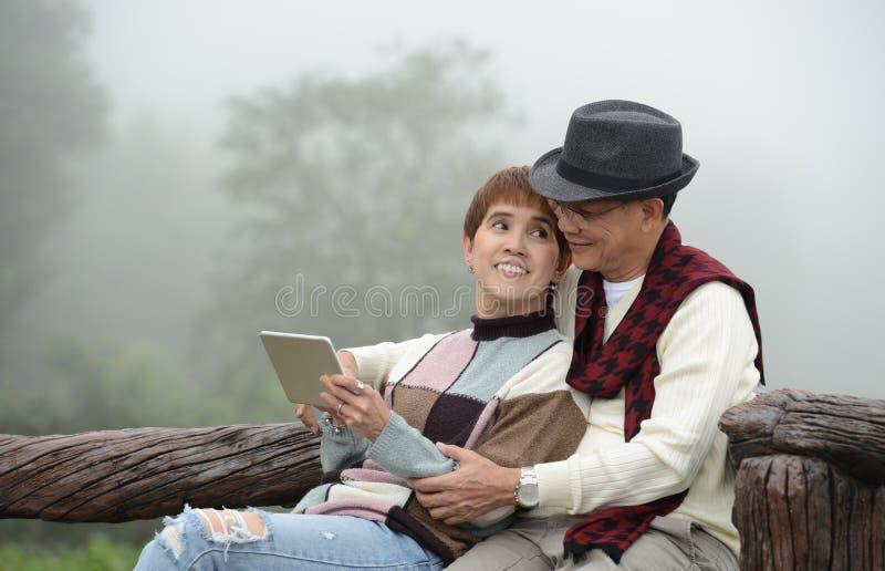 Pares superiores românticos usando a tabuleta digital foto de stock