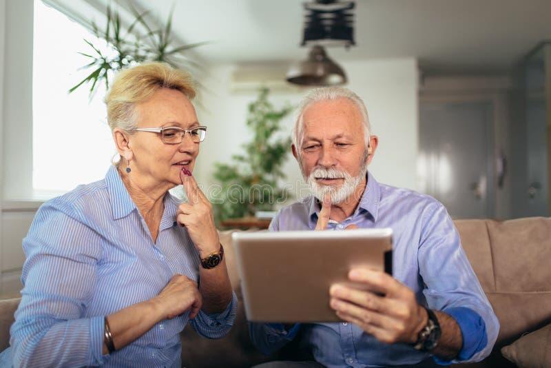 Pares superiores surdos de sorriso que falam usando a linguagem gestual na came da tabuleta digital fotografia de stock royalty free
