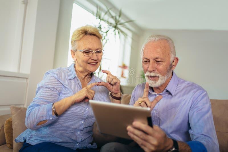 Pares superiores surdos que falam usando a linguagem gestual na came da tabuleta digital fotos de stock royalty free