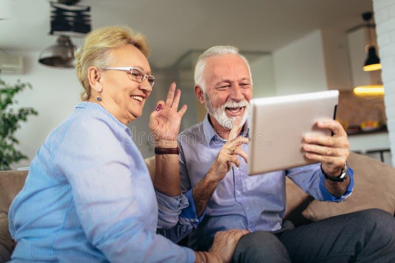 Pares superiores surdos que falam usando a linguagem gestual na came da tabuleta digital imagens de stock