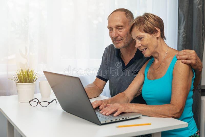 Pares superiores usando o laptop junto fotos de stock