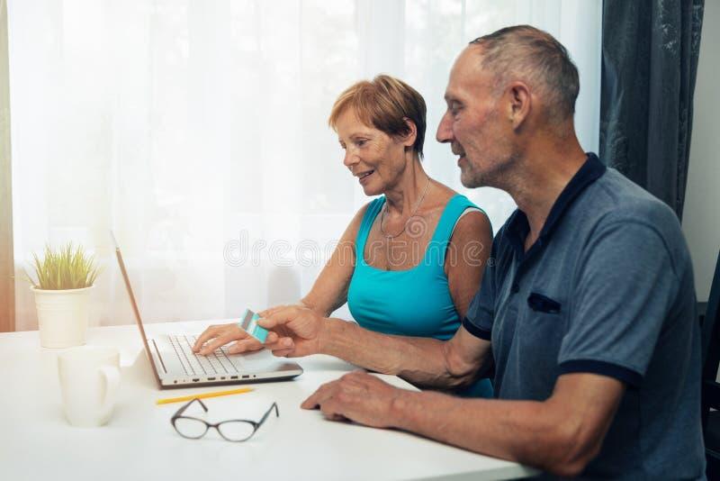 Pares superiores usando o portátil para a compra e os pagamentos do Internet foto de stock