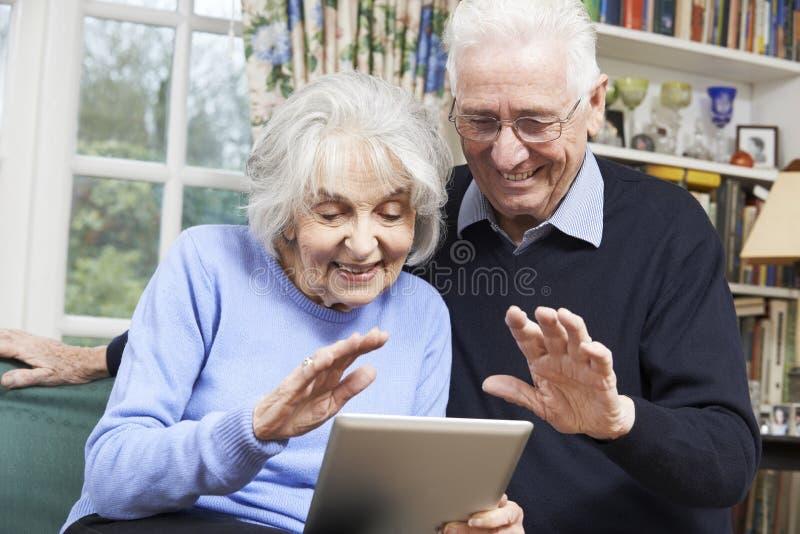 Pares superiores usando a tabuleta de Digitas para a chamada video com família fotografia de stock