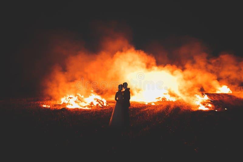 Pares surpreendentes do casamento perto do fogo na noite imagens de stock royalty free