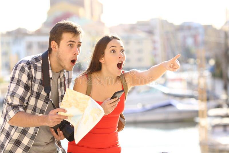 Pares surpreendidos de turistas que encontram o destino fotografia de stock