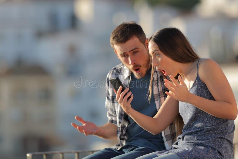 Pares surpreendidos que verificam o telefone esperto em uma cidade imagem de stock
