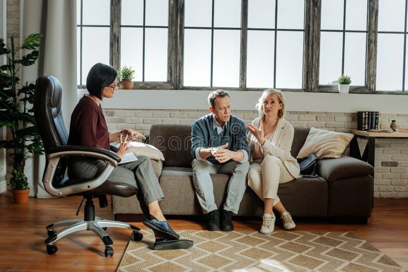 Pares tranquilos de la Edad Media que se sientan en el sofá durante la cita con el terapeuta imagen de archivo libre de regalías