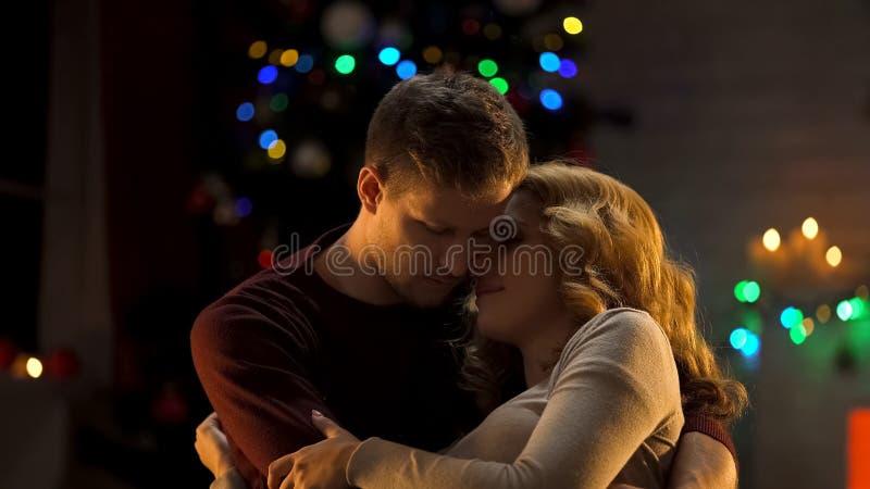 Pares trastornados que abrazan en el fondo de las luces de la Navidad, malas noticias el días de fiesta imágenes de archivo libres de regalías