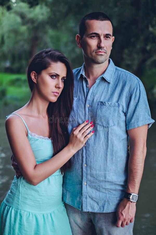 Pares tristes que estão pelo rio e que olham distante foto de stock royalty free