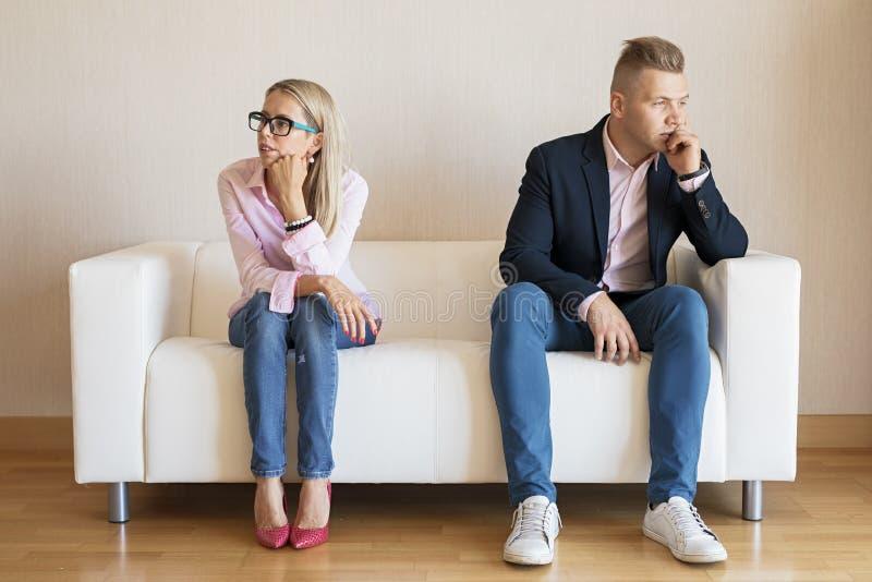 Pares tristes que se sientan en el sofá y que miran en diversas direcciones imagenes de archivo