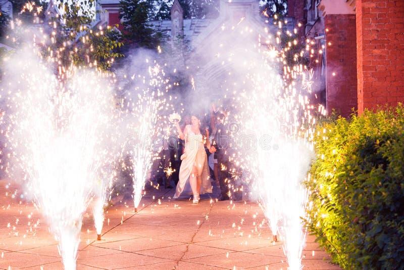 Pares Trought que camina de la boda las llamas de fuegos artificiales imagen de archivo