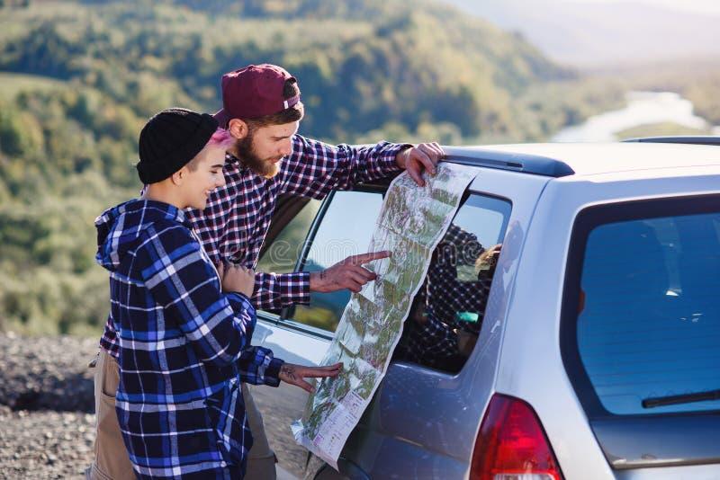 Pares turísticos felices con el mapa de papel cerca del coche Gente joven sonriente usando mapa El viajar en coche alquilado el v foto de archivo