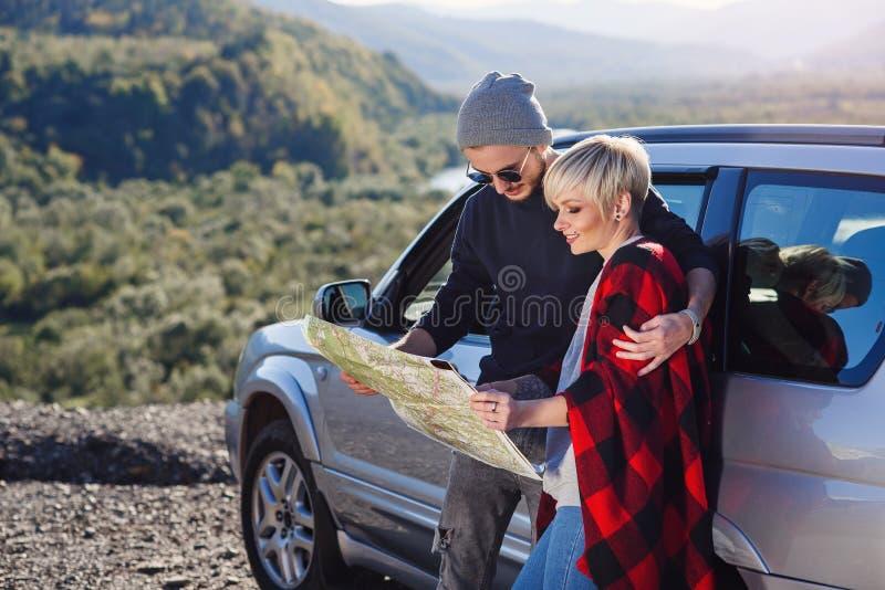 Pares turísticos felices con el mapa del papel cerca del coche alquilado Gente joven de moda usando mapa El viajar en coche el va fotografía de archivo