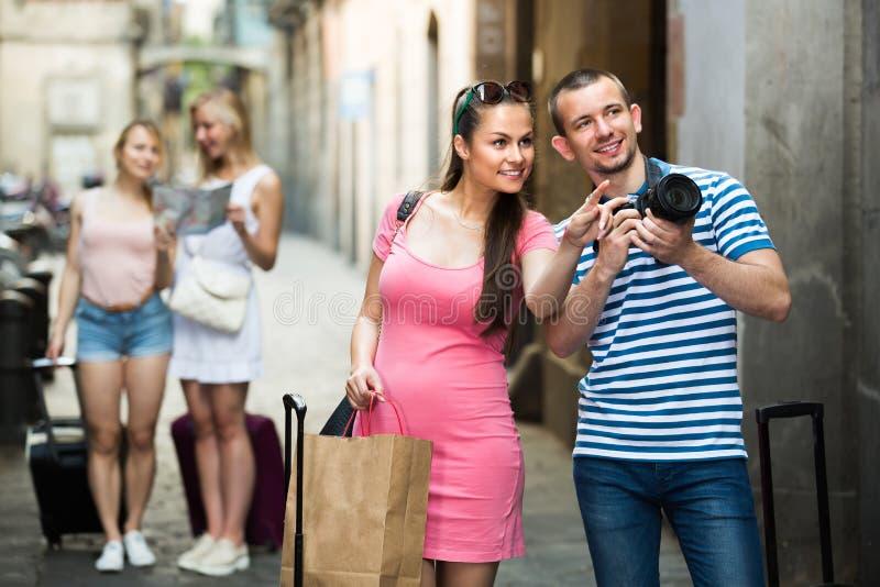Pares turísticos jovenes después de hacer compras al aire libre fotografía de archivo