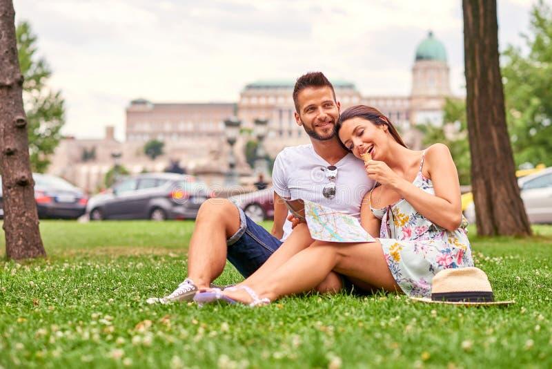 Pares turísticos jovenes en la hierba fotos de archivo